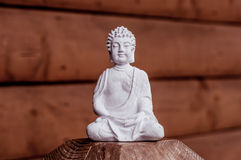 Zen, yoga and meditation concept. White Buddha on red wooden relax background Royalty Free Stock Photo