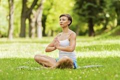 Zen yoga position woman on the grass. Stock Photos