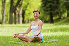 Zen yoga woman lotos position on the grass. Royalty Free Stock Images