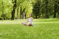 Zen yoga woman lotos position on the grass. Royalty Free Stock Image