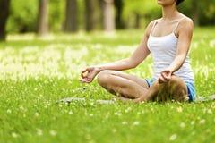Zen yoga woman lotos position on the grass. Stock Photos