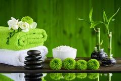Zenbasaltsteine und -badekurort auf dem Holztisch Lizenzfreie Stockbilder