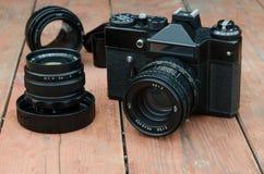 Zenit de la cámara del vintage con la lente y la película adicionales en el de madera Foto de archivo