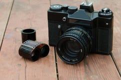 Zenit de la cámara del vintage con la película en el fondo de madera Fotografía de archivo