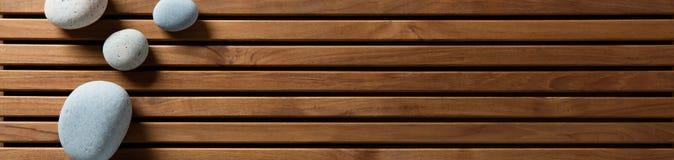 Zenkiezelstenen op ontwerp houten raad worden geplaatst, hoogste meningsbanner die royalty-vrije stock afbeelding