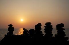 Zensteine auf dem Hintergrund des Sonnenuntergangs über dem Meer lizenzfreies stockbild