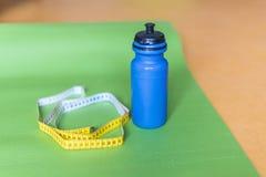 Zentimeterband, Yogamatte und Flasche Wasser an der Turnhalle Lizenzfreie Stockbilder