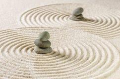 Zenträdgård med staplad stenar och sand med cirklar Arkivbild