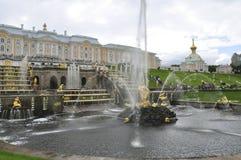 Zentraler Brunnen mit dem Palast und der Kirche auf dem Hintergrund in Peterhof, Russland stockfoto