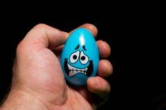 Zenuwachtig blauw paasei in de hand van iemand stock afbeeldingen