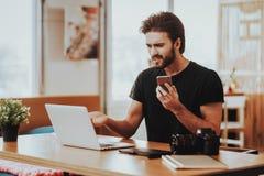 Zenuwachtig Guy Holds Phone Works op Laptop ver stock afbeeldingen