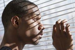 Zenuwachtige Afrikaanse Amerikaanse mens bij horizontaal venster, Royalty-vrije Stock Foto