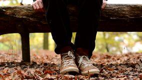 Zenuwachtige bored kerel op een bank in de herfstpark stock videobeelden