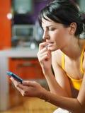Zenuwachtige cellphone van de vrouwenholding stock fotografie
