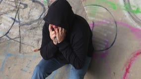 Zenuwachtige drugverslaafde bij een kleurrijke muur stock videobeelden