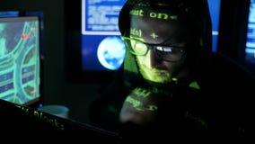 Zenuwachtige hakker die aan computer, Misdadig hakker barstend systeem werken, terwijl de groene codekarakters gezicht in dark ov stock video