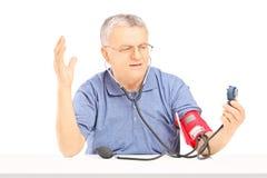 Zenuwachtige hogere mens die bloeddruk met sphygmomanomete meten Royalty-vrije Stock Foto's
