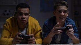 Zenuwachtige multiraciale kerels die computerspel verliezen, die elkaar, verslaving beschuldigen stock videobeelden