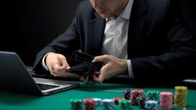 Zenuwachtige online gokker die lege portefeuille openen, weddend verslaving, faillissement stock foto
