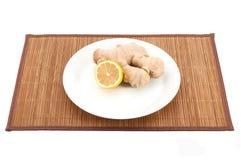 Zenzero e limone su un piatto bianco su una stuoia di bambù fotografia stock libera da diritti