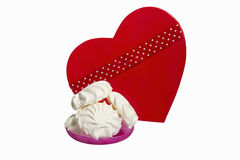 Zephyr with red hert hape box. White zephyr on pink saucer with red heart shape box  isolted on background Royalty Free Stock Image