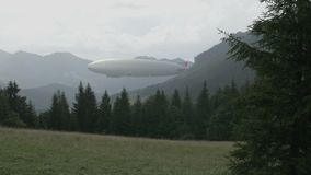 Zeppelin airship in landscape with wooden hills. Legendary huge flying balloon flies through mountain valley. Big dirigible, spruces in foreground, spinning stock video footage