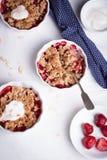 Zerbröckeln Sie mit Hafermehl, Vollkorn und Erdbeere in den weißen Schüsseln Lizenzfreie Stockfotos