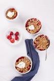 Zerbröckeln Sie mit Hafermehl, Vollkorn und Erdbeere in den weißen Schüsseln Stockfotos