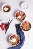 Zerbröckeln Sie mit Hafermehl, Vollkorn und Erdbeere in den weißen Schüsseln Lizenzfreie Stockfotografie
