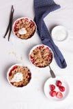 Zerbröckeln Sie mit Hafermehl, Vollkorn und Erdbeere in den weißen Schüsseln Stockfotografie