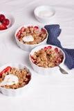Zerbröckeln Sie mit Hafermehl, Vollkorn und Erdbeere in den weißen Schüsseln Stockfoto