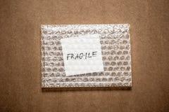 Zerbrechlich, Handschrift auf weißem squre Papier in der Luftpolsterfolie, Hintergrund des dunkelbraunen Kraftpapiers stockfotografie