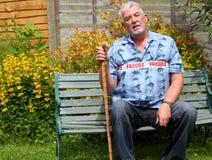 Zerbrechlicher älterer Mann, der mit Stock sitzt Lizenzfreies Stockbild