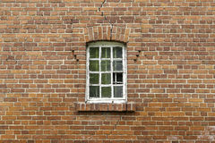 Zerbrochene Fensterscheibe auf Backsteinmauer Stockfotos