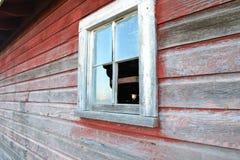 Zerbrochene Fensterscheibe auf einer Scheune Stockbilder