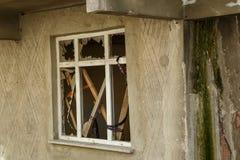 Zerbrochene Fensterscheibe eines unfertigen Hauses stockfotografie