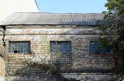 Zerbrochene Fensterscheiben in einem Altbau aufgrund einer verlassenen Fabrik Stockfotografie