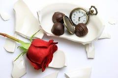 Zerbrochene Schüssel mit einer Rose und Schokoladen Lizenzfreie Stockfotografie