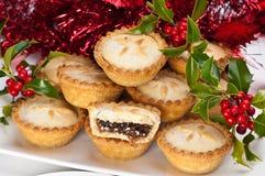 Zerkleinern Sie Torten für Weihnachten mit Stechpalme und Beeren stockfoto
