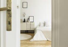 Zerknięcie przez drzwi w i gabinetów stoi na drewnianej podłoga monochromatic, białego sypialni wnętrze z łóżkiem, Istna fotograf obrazy stock