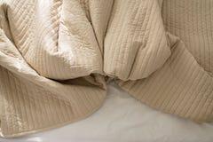 Zerknitterte Decken auf Bett nach morgens aufwachen, Sahnefarbe getont lizenzfreie stockbilder