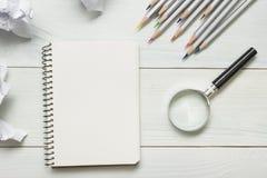 Zerknitterte Papierbälle, Lupe, Bleistifte und Notizbuch mit leerem weißem Blatt auf Holztisch Kreativitätskrise Stockfoto