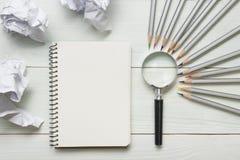 Zerknitterte Papierbälle, Lupe, Bleistifte und Notizbuch mit leerem weißem Blatt auf Holztisch Kreativitätskrise Lizenzfreies Stockbild