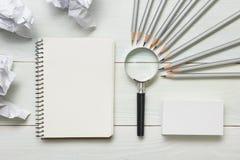 Zerknitterte Papierbälle, Lupe, Bleistifte und Notizbuch mit leerem weißem Blatt auf Holztisch Kreativitätskrise Lizenzfreies Stockfoto