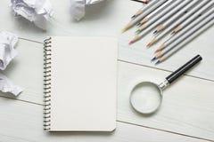 Zerknitterte Papierbälle, Lupe, Bleistifte und Notizbuch mit leerem weißem Blatt auf Holztisch Kreativitätskrise Lizenzfreie Stockfotografie