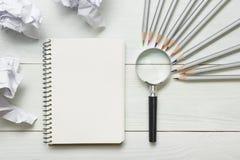 Zerknitterte Papierbälle, Lupe, Bleistifte und Notizbuch mit leerem weißem Blatt auf Holztisch Kreativitätskrise Lizenzfreie Stockfotos