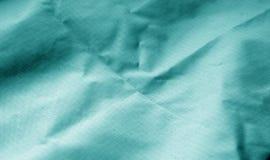 Zerknitterte Textiloberfläche in der cyan-blauen Farbe lizenzfreie stockfotos