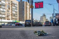 Zerknitterter Dollar auf der Fußgängerpflasterung mit Geldumtausch veranschlagt auf dem Hintergrund Stockbild