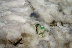 Zerknitterter Dollar im Schnee auf dem streen Stockbild