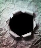 Zerknitterter Papierhintergrund mit dem großen schwarzen Loch durch gelocht Lizenzfreies Stockbild